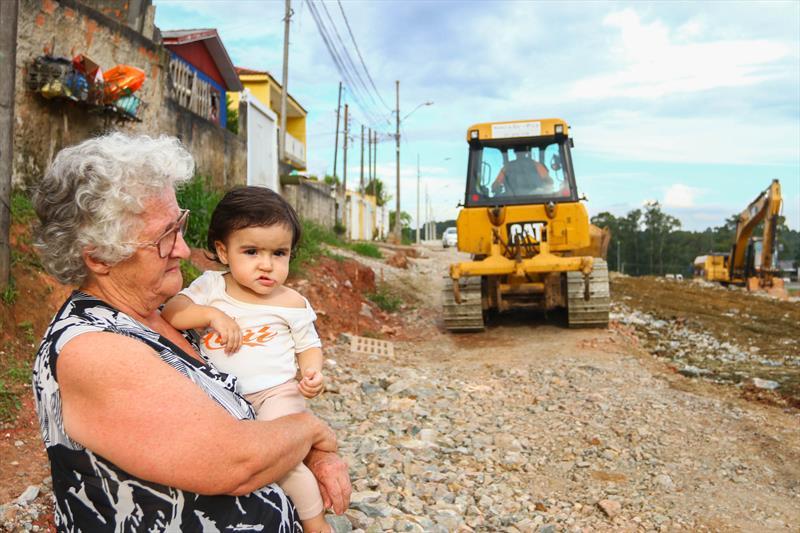 """Em breve, o Viaduto Pompéia, no Tatuquara, estará cumprindo a função para a qual foi criado. A estrutura foi entregue em setembro de 2015 pela Autopista Planalto Sul/Arteris - concessionária responsável pela rodovia BR-116 - mas sem as alças necessárias para os motoristas acessarem o viaduto. As alças deveriam ter sido construídas pela gestão anterior, mas só a partir de setembro de 2018 foram iniciadas. Moradora da Rua Francisco Xavier de Oliveira há 44 anos, a dona de casa Nilce Oliboni não vê a hora de a obra ficar pronta. """"Esperamos por tantos anos, enfrentamos agora alguns transtornos, mas vai ficar melhor. Nosso bairro e nossa rua ficarão mais bonitos e melhores para se viver"""", disse dona Nilce com a bisneta Izabela no colo. - Curitiba, 22/02/2019 - Foto: Daniel Castellano / SMCS"""