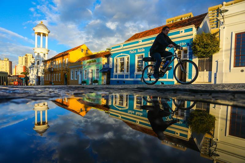Ciclista pedala após a chuva na Praça Garibaldi, Largo da Ordem, Centro histórico de Curitiba. Foto: Daniel Castellano