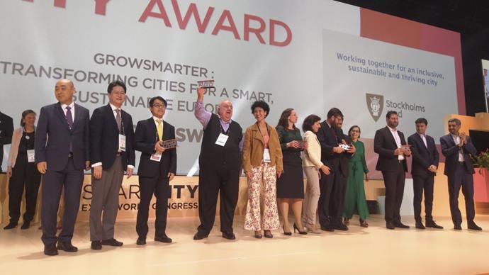 Prefeito Rafael Greca ergue troféu, ao lado de Cris Alessi (presidente da Agência Curitiba) e de representantes das demais cidades finalistas do World Smart City Awards 2019, em Barcelona.  Foto: Divulgação
