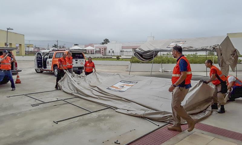 Com o apoio de voluntários, a Defesa Civil de Curitiba começou a montagem de dez barracas que poderão ser utilizadas como ponto de apoio ou espaço para triagem de pacientes com problemas respiratórios. Foto: Divulgação