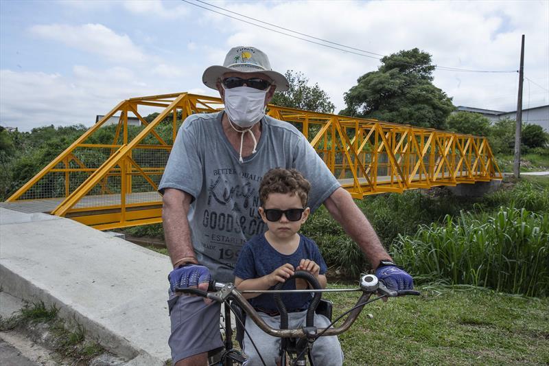 Nova passarela oferece mais segurança a moradores do Bairro Alto. Na imagem: Osnir Pamplona e seu neto Gabriel. Curitiba, 12/01/2021. Foto: Ricardo Marajó/SMCS
