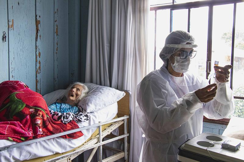 Idosos acamados começam a ser vacinado pelas equipes da Saúde de Curitiba. A técnica de enfermagem Juliana Cristina, prepara a vacina para aplicar na Dona Brandina Jacomasso. Curitiba, 08/02/2021. Foto: Ricardo Marajó/SMCS