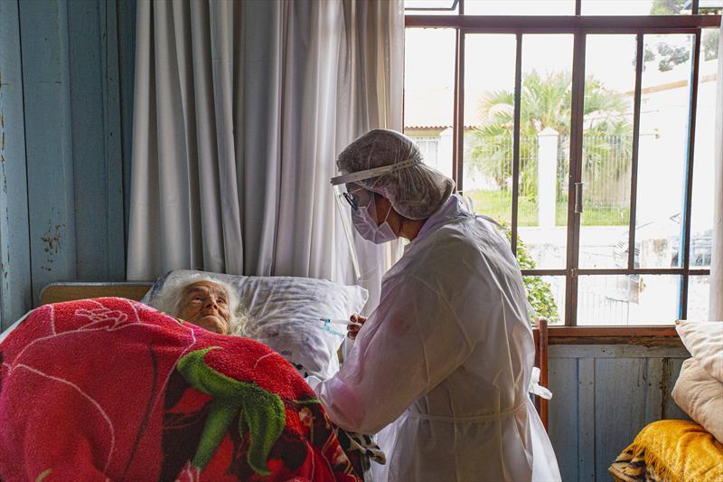 Idosos acamados começam a ser vacinado pelas equipes da Saúde de Curitiba. A técnica de enfermagem Juliana Cristina, aplica a vacina na Dona Brandina Jacomasso. Curitiba, 08/02/2021. Foto: Ricardo Marajó/SMCS