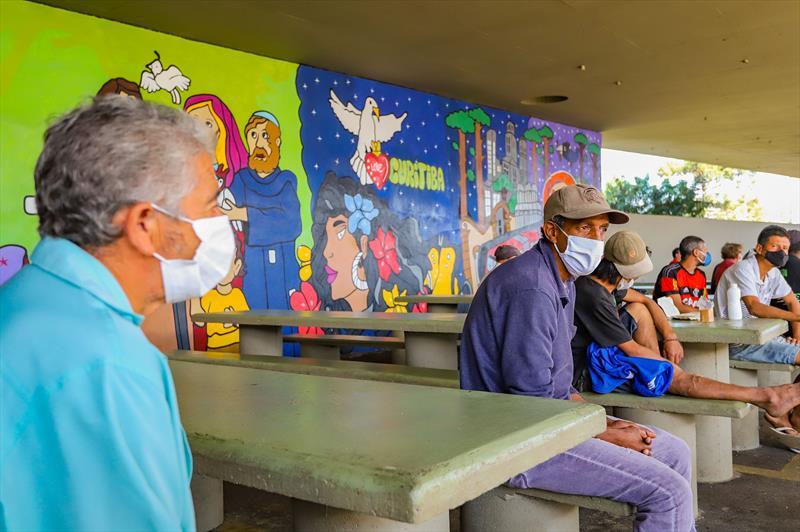 Moradores em situação de rua fazem sua refeição nas mesas da Praça Plinio Tourinho que faz parte do Programa mesa Solidária.  Curitiba, 09/04/2021.  Foto: Daniel Castellano/SMCS