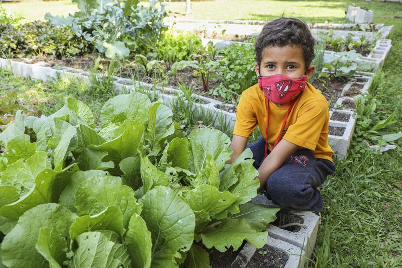 O estudante Alex Gabriel Liberato Silva, 7 anos, está encantado com o crescimento das mudas nas últimas semanas na horta da escola municipal na CIC. Curitiba, 20/09/2021. Foto: Hully Paiva/SMCS